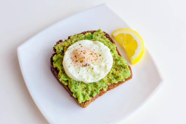 Homemade avocado toast with rye bread, egg on top and slice of lemon