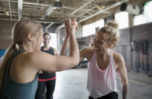 Strong, enthusiastic women high-fiving in gym